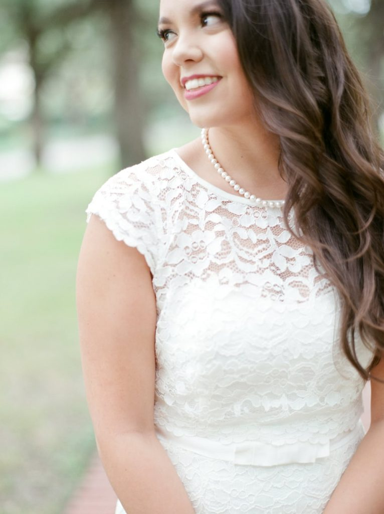A chic strand of pearls over a white lace dress - such a timeless look!