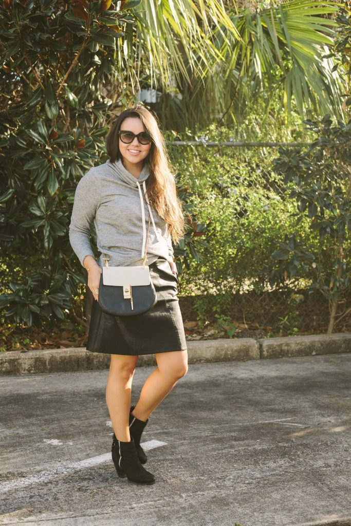 faux leather skirt paired with booties makes for a great mild winter weather look