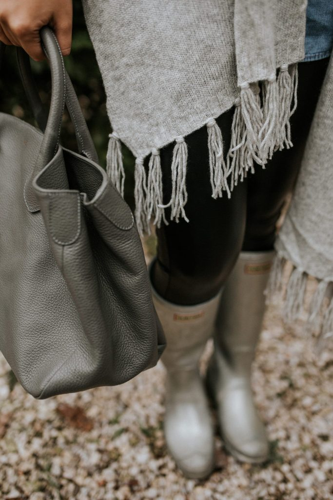 shades of grey in a fringe wrap, top handle purse and metallic silver hunter rain boots