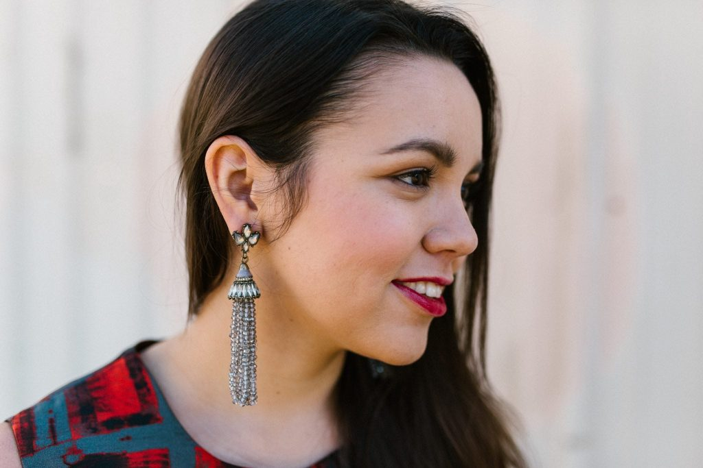 silver beaded tassel earrings and bold lipstick