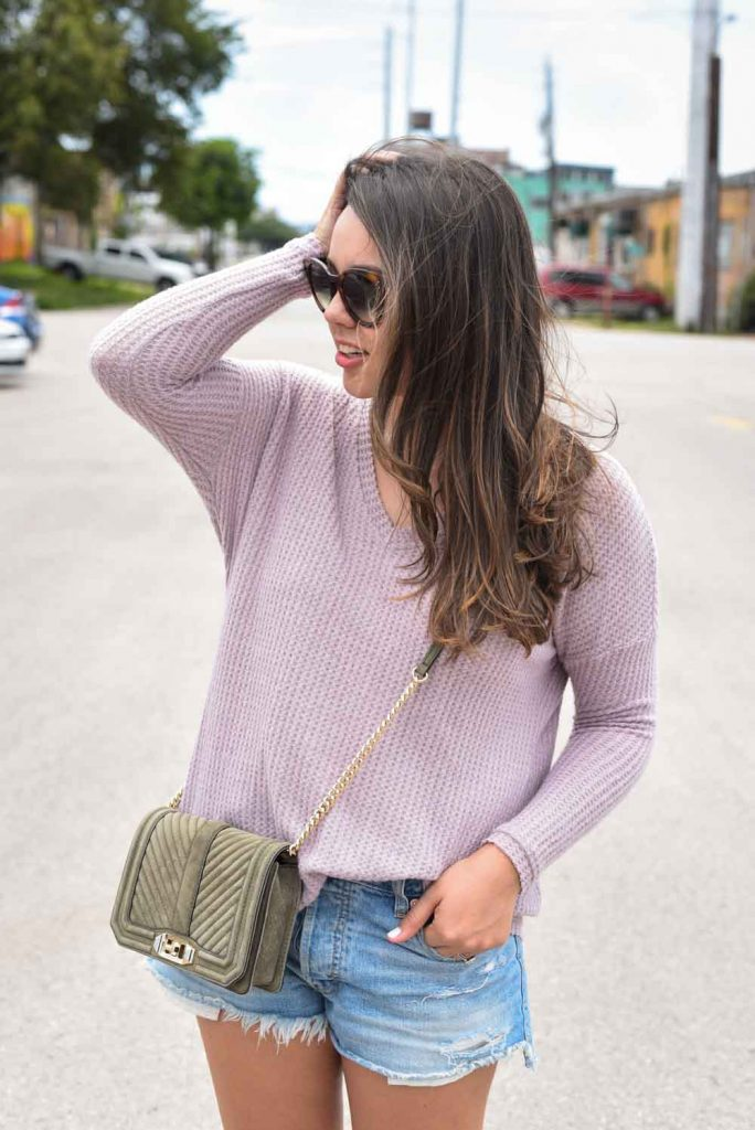 Lilac pullover, denim cut-off shorts, crossbody purse